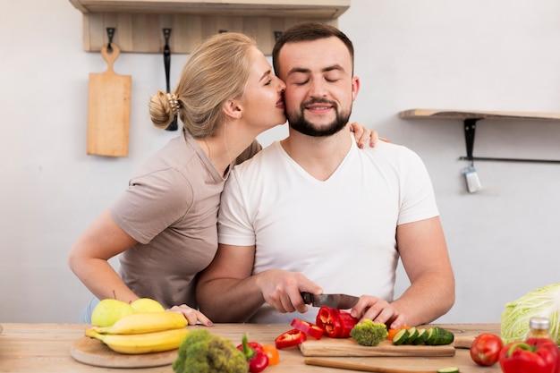 Casal fofo cozinhando na cozinha Foto gratuita