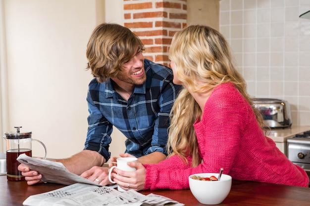 Casal fofo lendo o jornal na cozinha Foto Premium