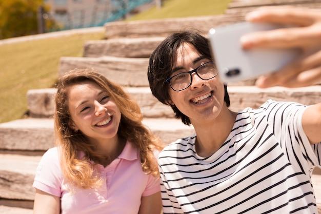Casal fofo multirracial, sorrindo para a câmera Foto gratuita