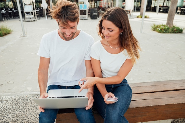 Casal fofo num banco com laptop Foto gratuita