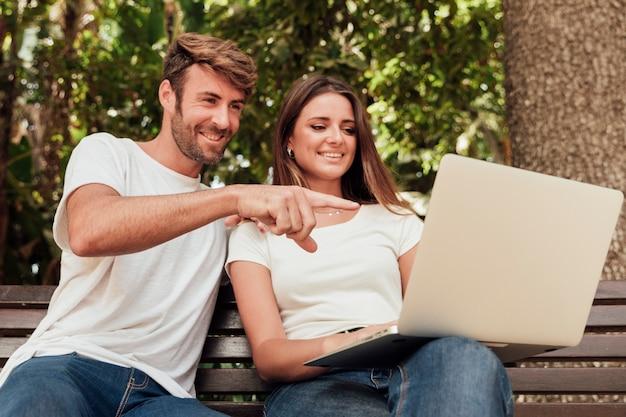 Casal fofo num banco com um notebook Foto gratuita