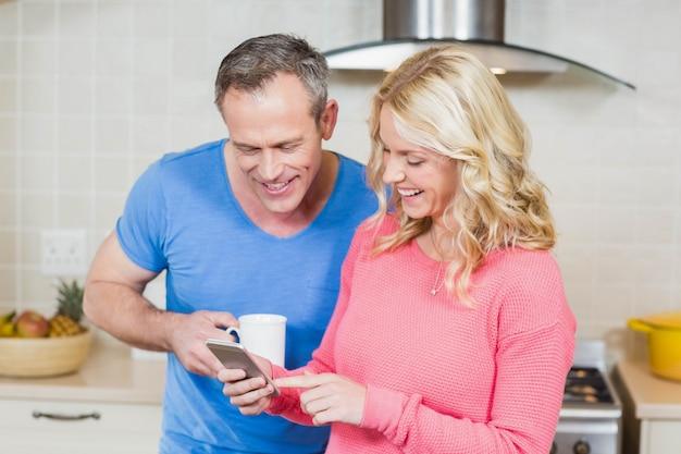 Casal fofo olhando para smartphone na cozinha Foto Premium