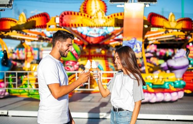 Casal fofo segurando sorvetes na feira Foto gratuita