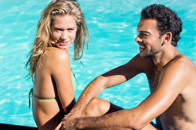 Casal fofo sentado à beira da piscina Foto Premium