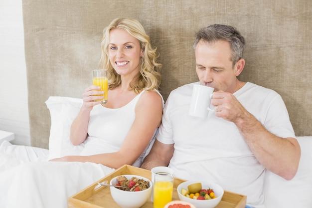 Casal fofo tomando café da manhã na cama no seu quarto Foto Premium