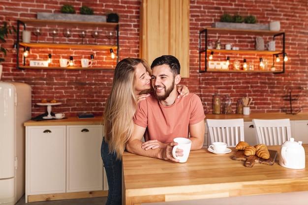 Casal fofo tomando café da manhã na cozinha Foto gratuita