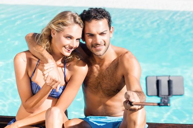 Casal fofo tomando selfie à beira da piscina Foto Premium