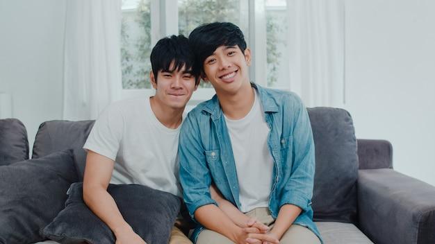 Casal gay asiático novo do retrato que sente feliz sorrindo em casa. os homens asiáticos lgbtq relaxam o sorriso, olhando para a câmera enquanto estava deitado no sofá na sala de estar em casa pela manhã. Foto gratuita