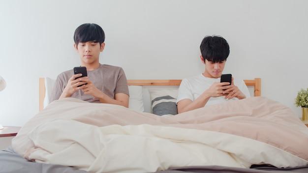 Casal gay asiático usando telefone celular em casa. jovens asiáticos lgbtq + homens felizes relaxam descansar juntos depois de acordar, verifique as mídias sociais, deitada na cama no quarto em casa de manhã. Foto gratuita