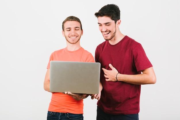 Casal gay feliz olhando para notebook Foto gratuita