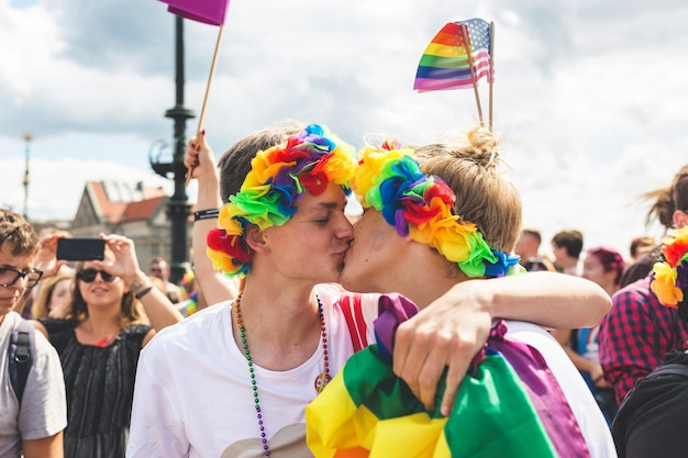Casal gay se beijando no meio da multidão no desfile lgbt Foto Premium