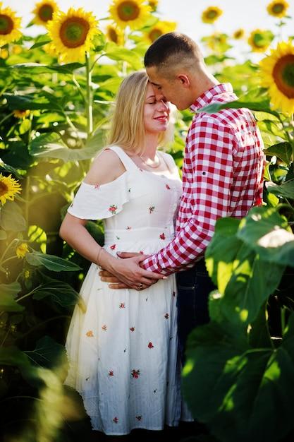 Casal grávida no campo de girassóis. momentos de gravidez Foto Premium
