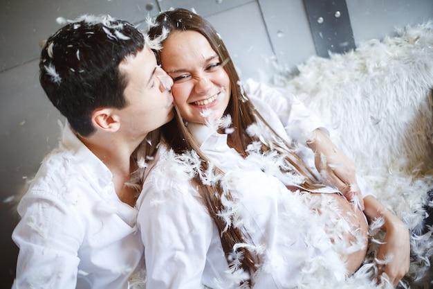 Casal grávida se divertindo, luta de almofadas Foto Premium