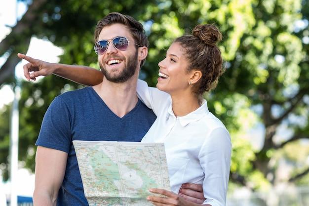 Casal hip verificar mapa e apontando em algum lugar da cidade Foto Premium