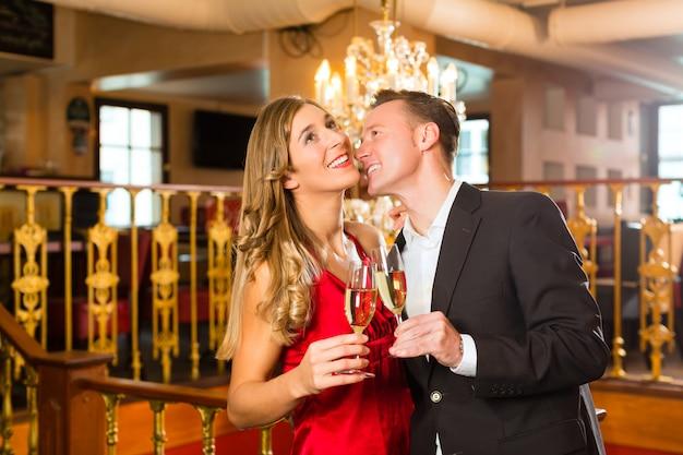 Casal, homem e mulher, bebendo champanhe em um restaurante requintado, cada um com uma taça de vinho espumante na mão, um grande lustre está Foto Premium