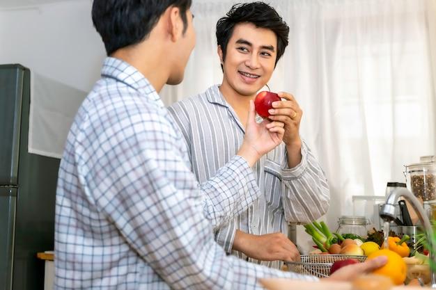 Casal homossexual asiático feliz e engraçado cozinhar salada na cozinha. conceito lgbt gay. Foto Premium