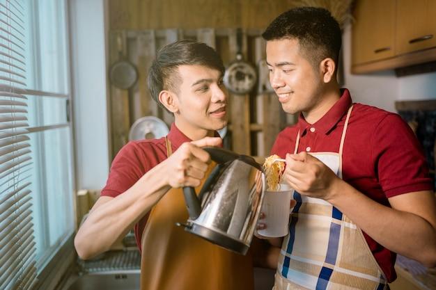 Casal homossexual masculino cozinhar um copo de macarrão instantâneo Foto Premium