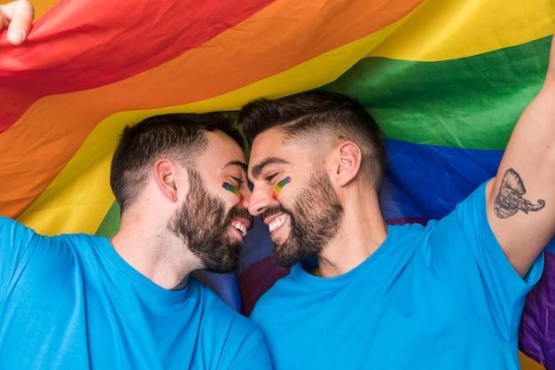 Casal homossexual suavemente carinhos na bandeira do arco-íris Foto gratuita