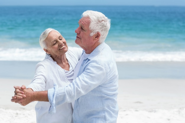 Casal idoso dançando na praia   Foto Premium
