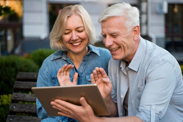 Casal idoso sorridente acenando para alguém com quem está conversando no tablet Foto gratuita