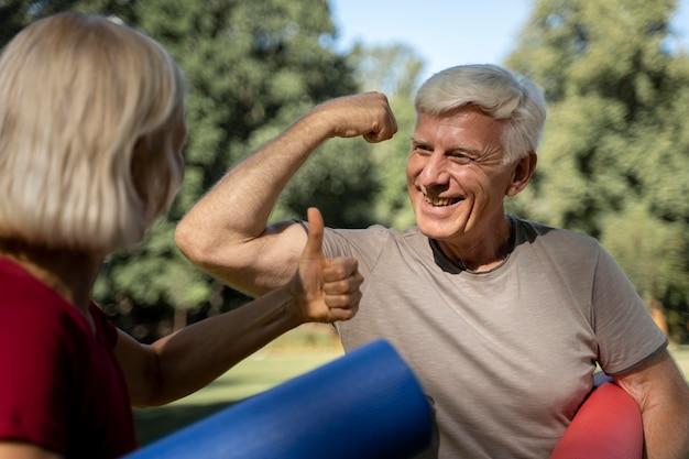 Casal idoso sorridente ao ar livre com esteiras de ioga Foto Premium
