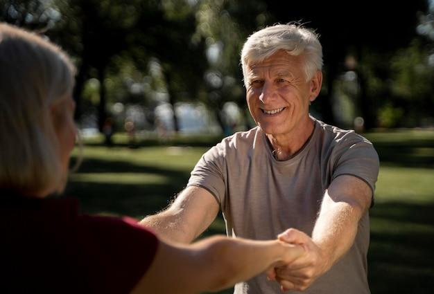 Casal idoso sorridente fazendo exercícios ao ar livre Foto gratuita