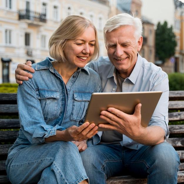 Casal idoso sorridente olhando para algo no tablet Foto gratuita