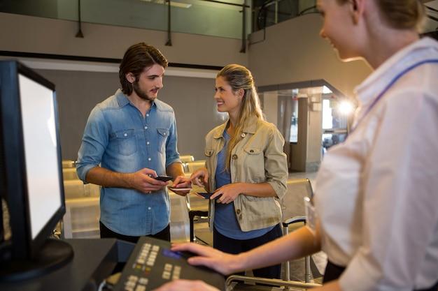 Casal interagindo um com o outro no balcão de check in Foto gratuita