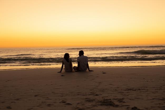Casal interagindo uns com os outros na praia durante o pôr do sol Foto gratuita
