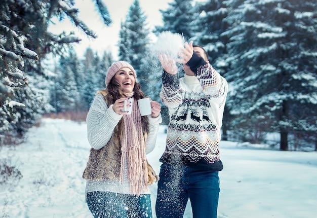 Casal jogando neve na floresta de inverno Foto Premium