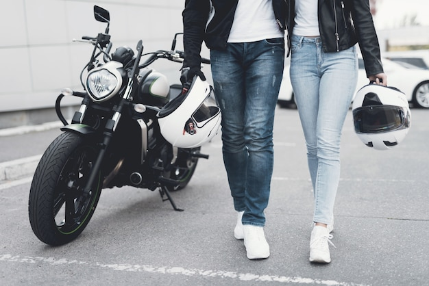 Casal jovem andando longe da motocicleta Foto Premium