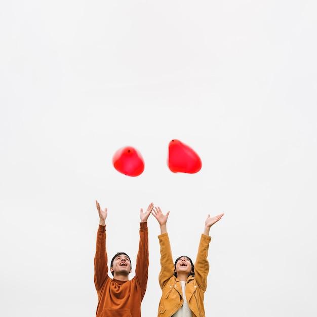 Casal jovem animado deixando ir balões Foto gratuita