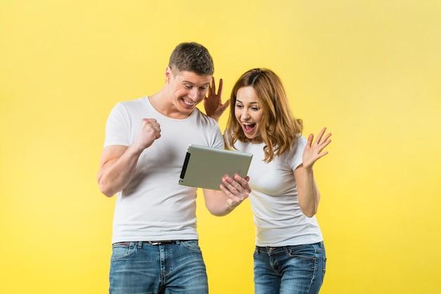 Casal jovem animado olhando tablet digital contra pano de fundo amarelo Foto gratuita