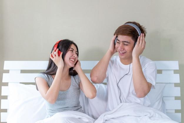 Casal jovem asiático sentado na cama e usando fones de ouvido para ouvir música e dançar alegremente Foto gratuita