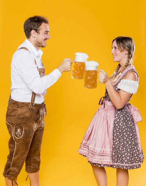 Casal jovem bávaro, brindando cervejas Foto gratuita
