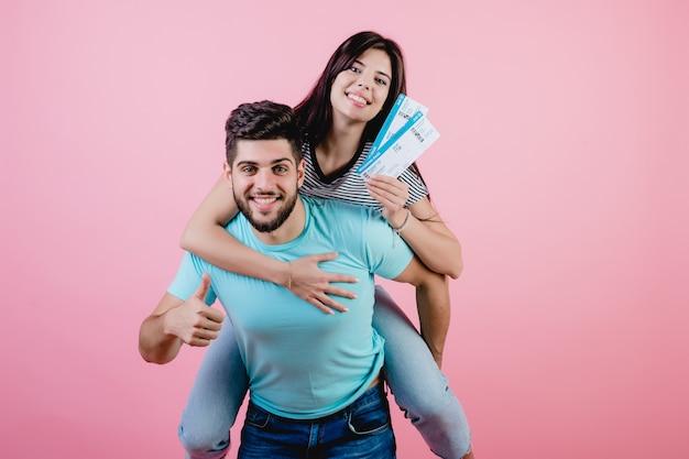 Casal jovem bonito com bilhetes de avião, namorado segurando a namorada imitando o avião Foto Premium