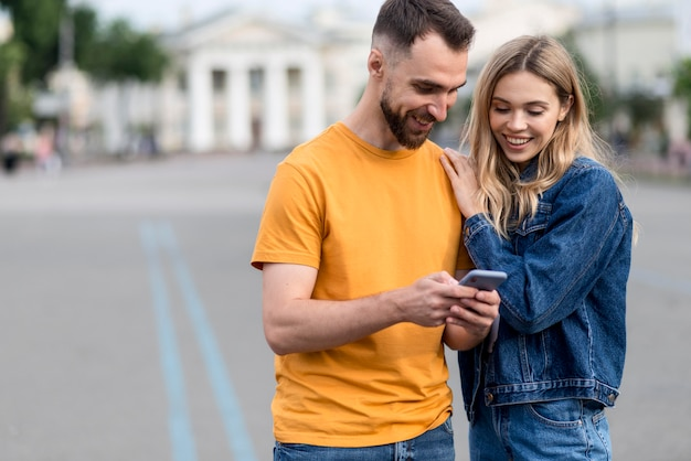 Casal jovem bonito olhando para um telefone Foto gratuita