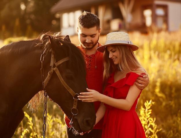 Casal jovem charmoso fica com um cavalo marrom antes de uma casa de campo Foto gratuita