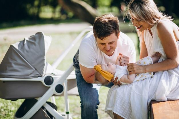 Casal jovem com sua filha bebê no parque sentado por carrinho de bebê ther Foto gratuita