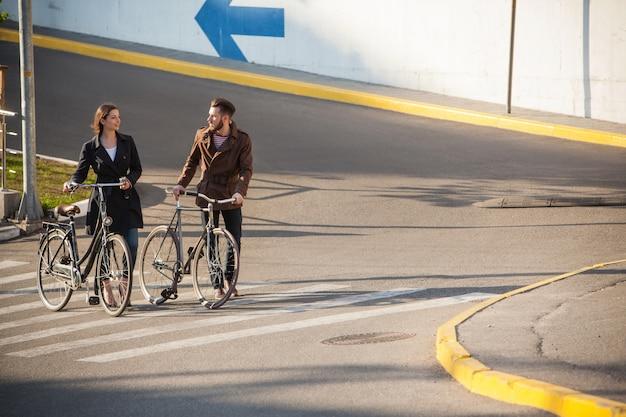 Casal jovem com uma bicicleta em frente à cidade Foto gratuita