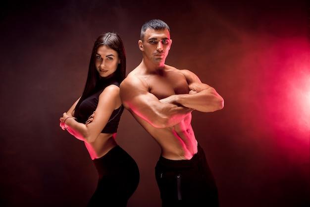 Casal jovem desportivo na parede preta Foto Premium