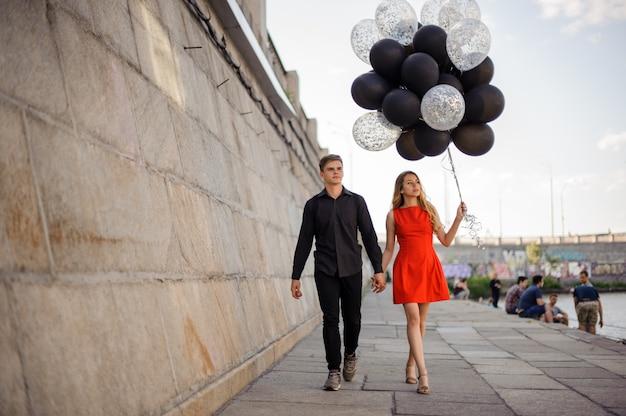Casal jovem e bonito caminha ao longo do passeio Foto Premium