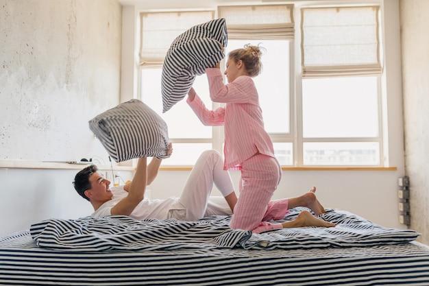 Casal jovem e bonito se divertindo na cama pela manhã fica junto em casa sozinho Foto gratuita