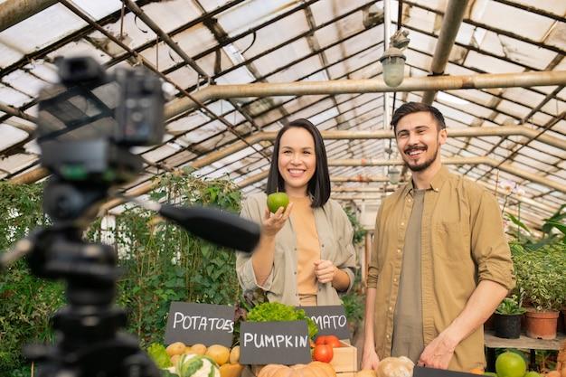 Casal jovem e saudável alegre em pé à mesa com legumes e contando sobre os benefícios dos alimentos orgânicos durante a filmagem do vídeo Foto Premium