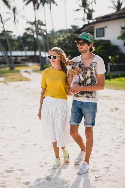 Casal jovem elegante e moderno apaixonado, andando e brincando de cachorro Foto gratuita