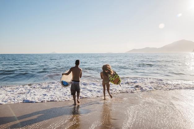 Casal jovem em um dia de surf Foto gratuita