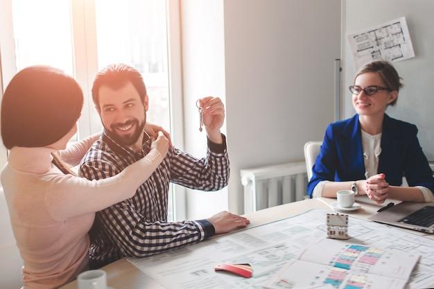 Casal jovem família compra alugar imóveis. agente dando consulta para homem e mulher. assinatura de contrato para compra de casa, apartamento ou apartamento. fornecendo chaves para alguns clientes. Foto Premium