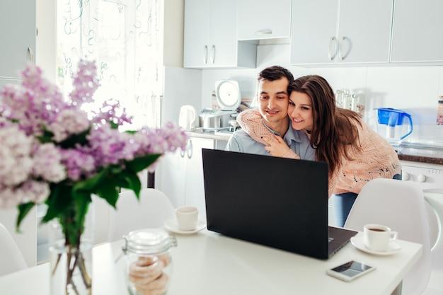 Casal jovem feliz auto isolado em casa usando laptop bebendo café Foto Premium
