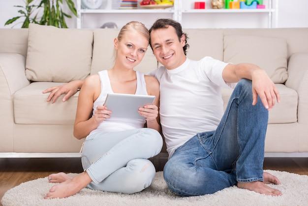 Casal jovem feliz com tablet em casa. Foto Premium