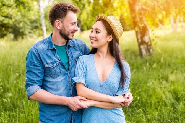 Casal jovem feliz de mãos dadas e sorrindo na natureza Foto gratuita